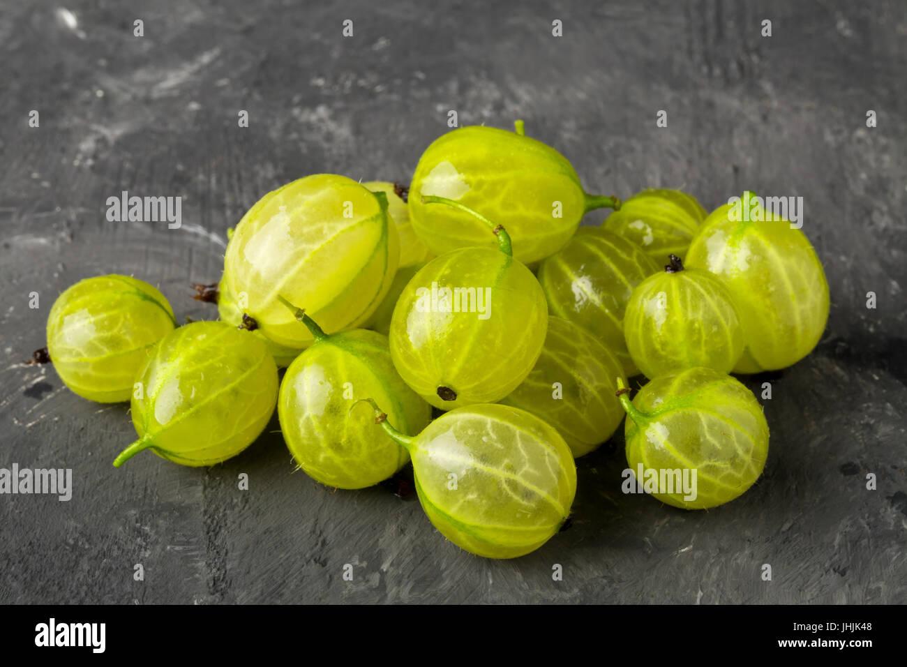 Haufen von Reife, frisch geerntete grüne Stachelbeere Früchte auf dunklem Hintergrund Stockbild