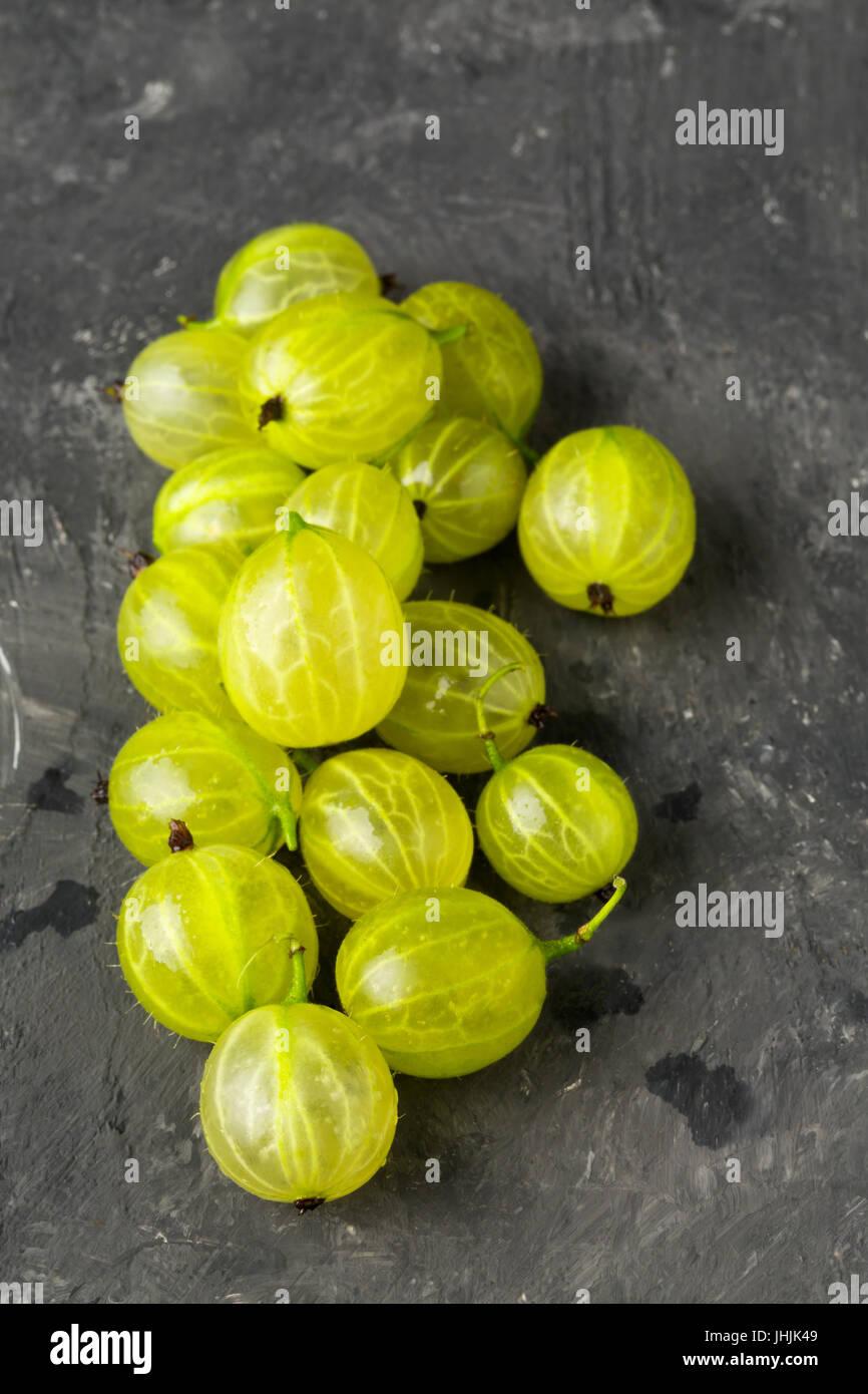 Haufen von Reife, frisch geerntete grüne Stachelbeere Früchte auf dunklem Hintergrund Stockfoto
