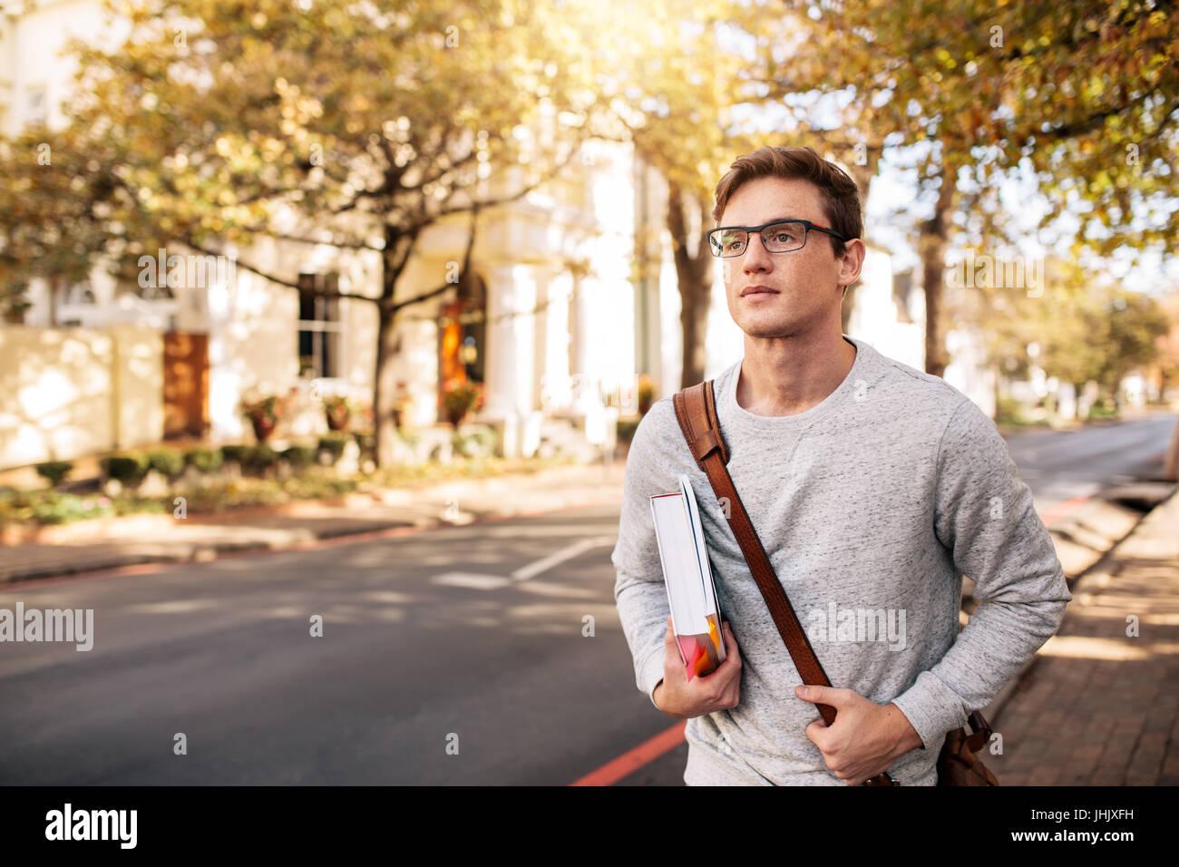 Kaukasische männliche Schüler mit Buch draußen auf der Straße. Hübscher junger Mann geht Stockbild