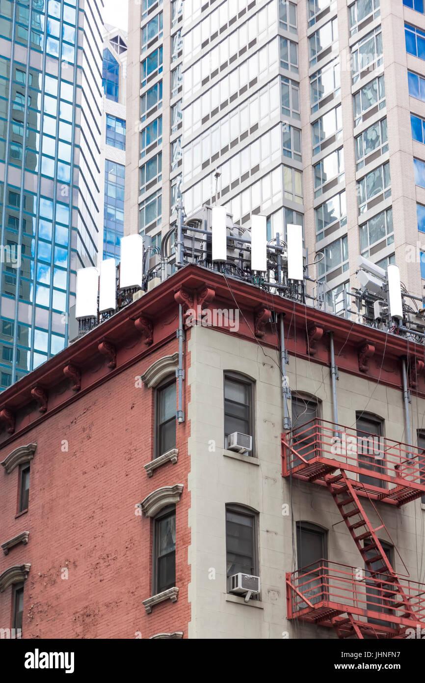 Handy-Antennen auf einem Flachbau Ecke Wohnhaus Dach in Midtown East, New York City, NY, Vereinigte Staaten Stockbild