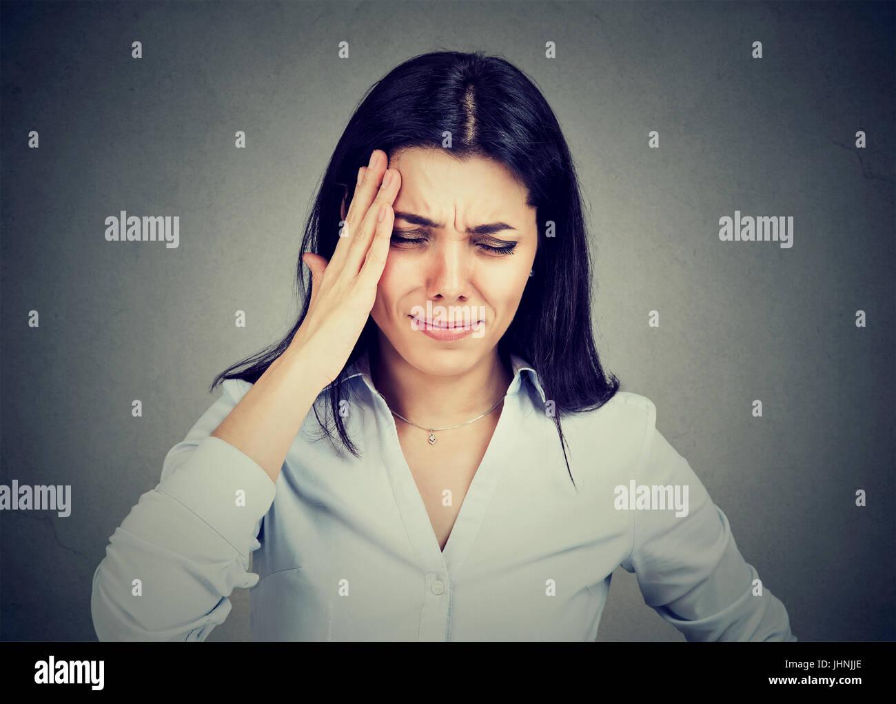 Junge Frau, die unter Kopfschmerzen leiden Stockbild