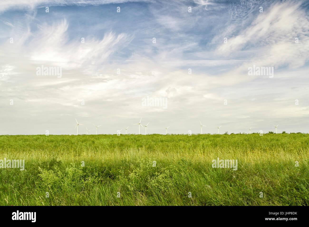 Windkraftanlagen im Green Field mit einem teilweise bewölkten Himmel. Stockbild