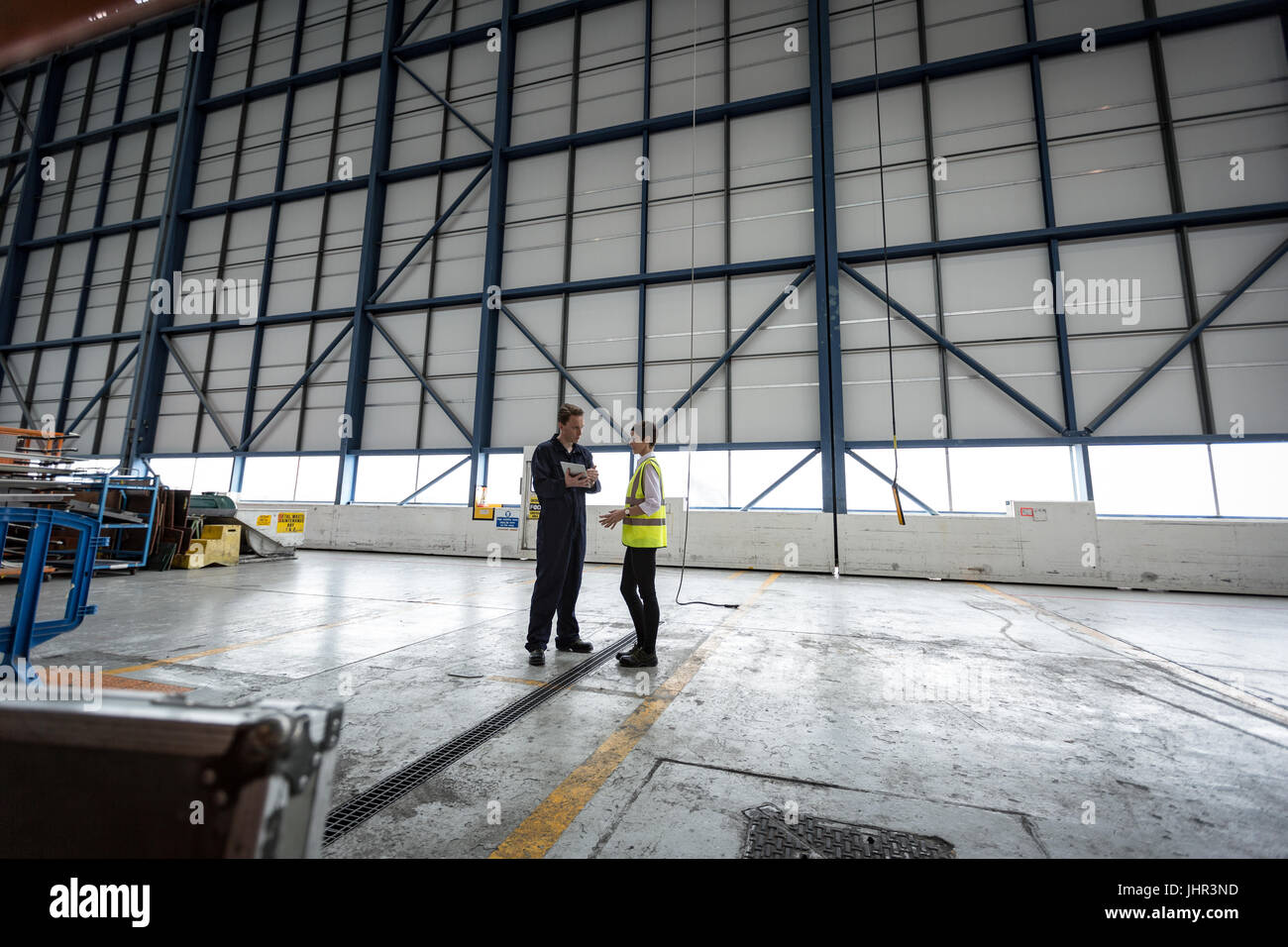 Wartungstechniker bei Fluggesellschaften Wartungseinrichtung miteinander interagieren Stockbild