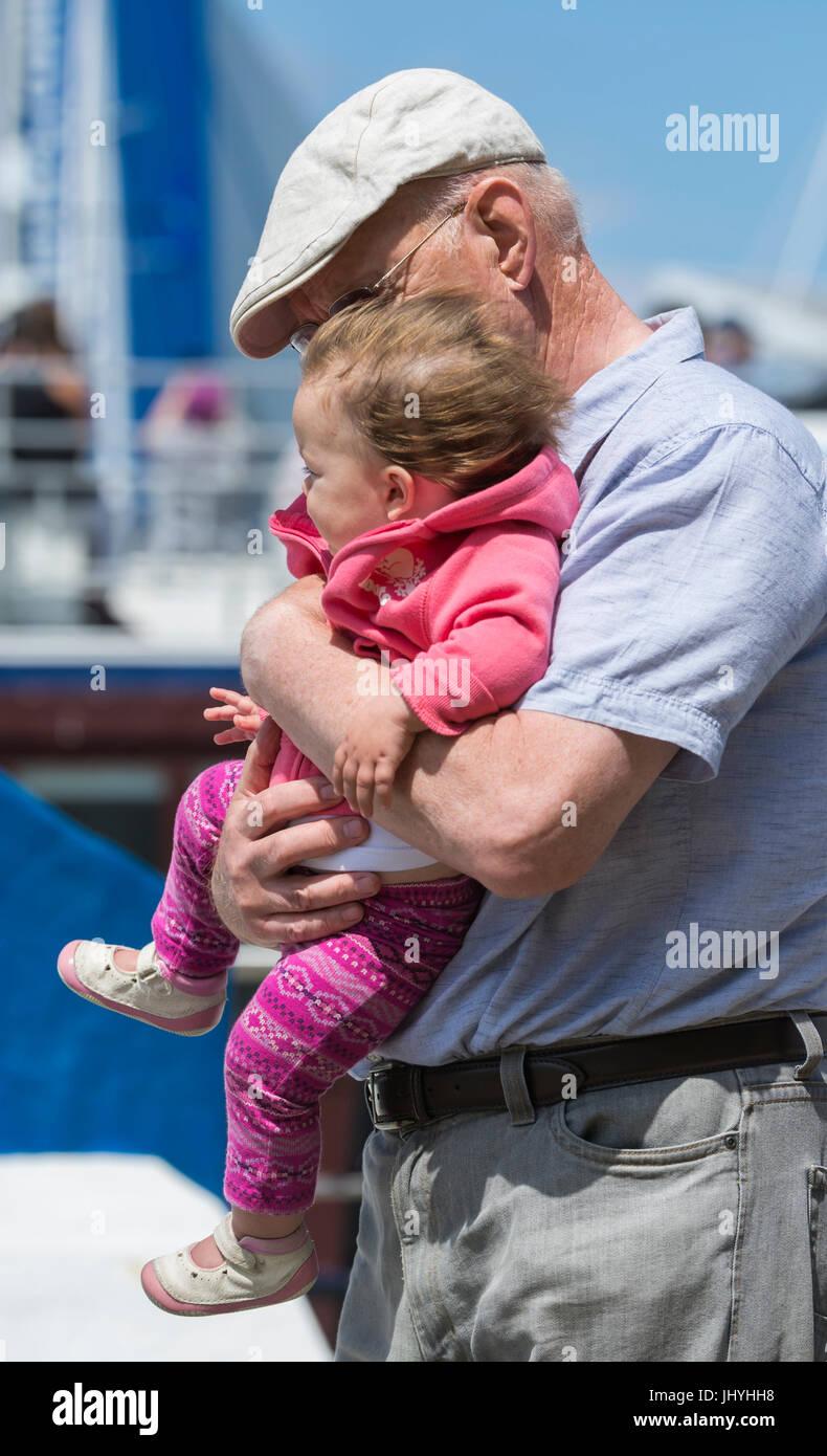 Älterer Mann ein junges Baby tragen. Großvater und Kind Bindung Konzept. Andere Generation Konzept. Stockbild
