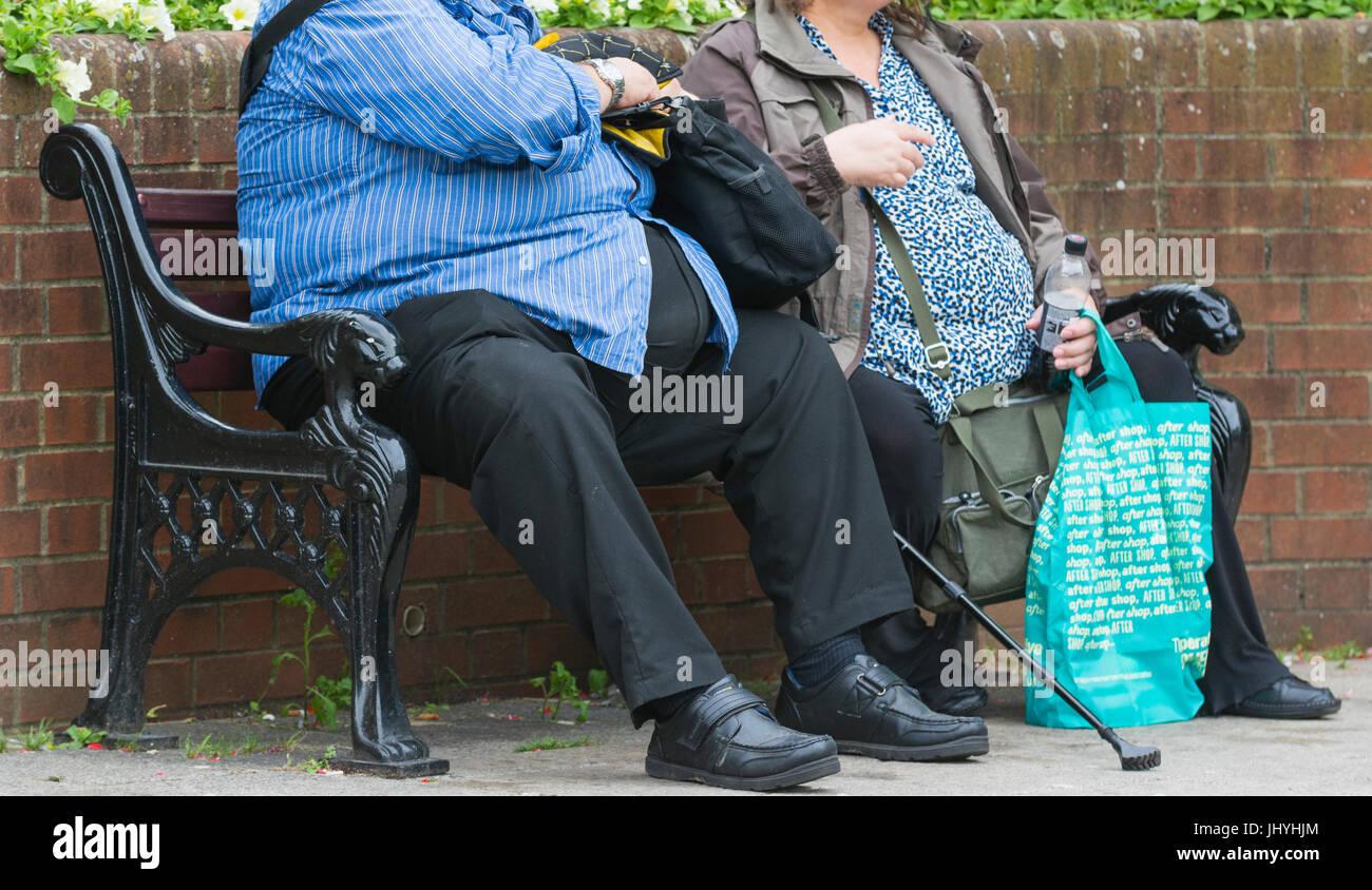 Krankhaft fettleibig. Übergewicht paar draußen sitzen auf einer Bank. Ungesunde Lebensweise. Stockbild