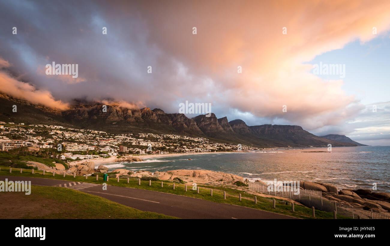 Sonnenuntergang und Wolken über Camps Bay, Tafelberg und den zwölf Aposteln, Cape Town, Südafrika, Stockbild