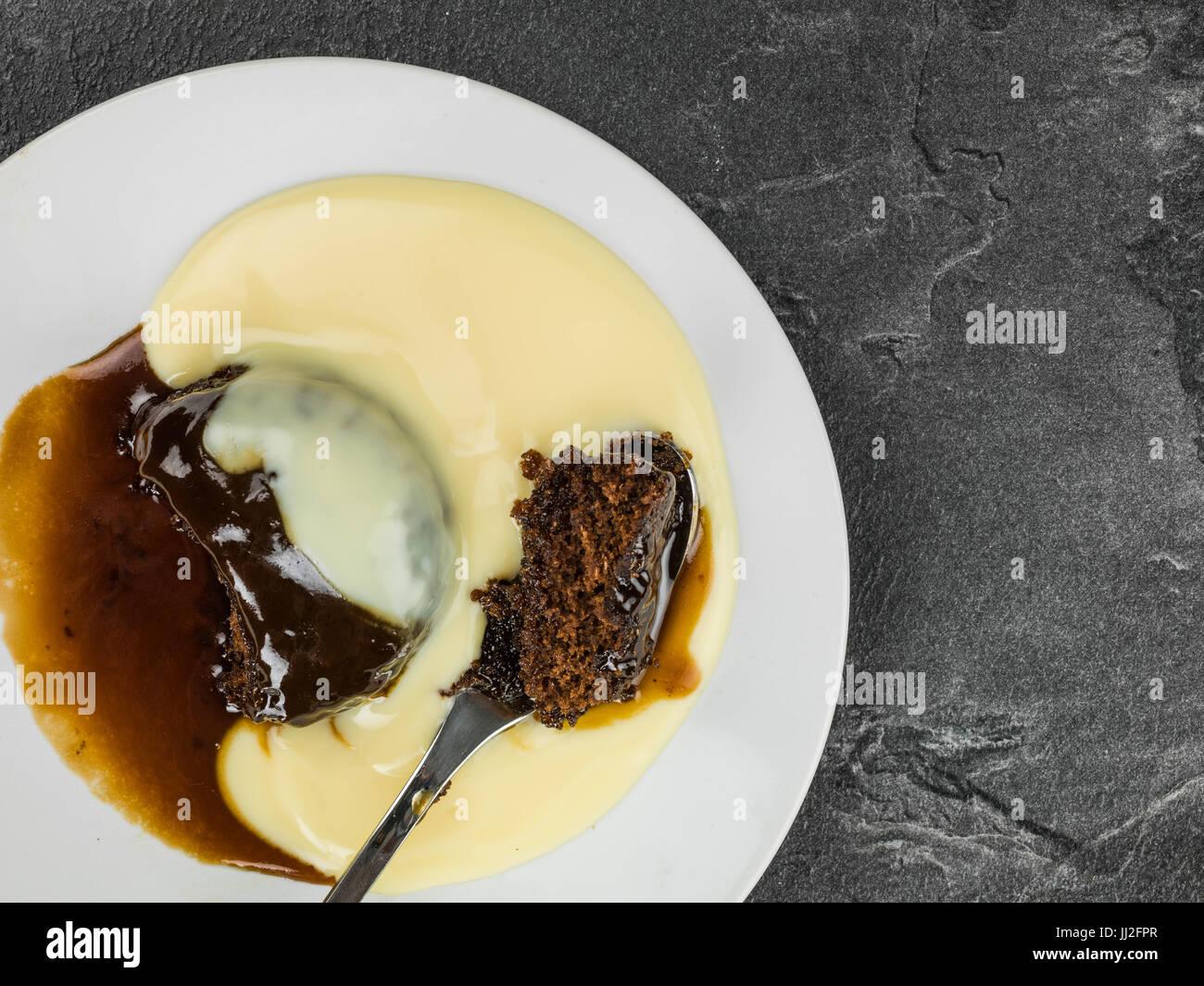 Sticky Toffee Pudding Dessert serviert mit warmen Pudding vor schwarzem Schiefer Hintergrund Stockbild