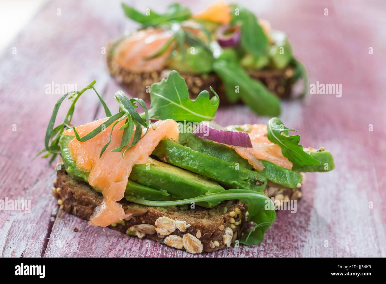 Countrybread Avocado, gesalzener Lachs Sandwich mit frischen Kräutern auf rosa craked Paintt Holzbrett Hintergrund. Stockbild