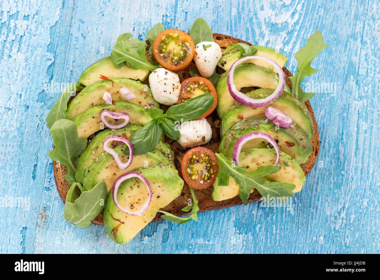 Vollkornbrot Avocado, Tomaten, Mozzarrela Sandwich mit frischen Kräutern, roten Zwiebeln auf Geschirrtuch Holzbrett Stockbild