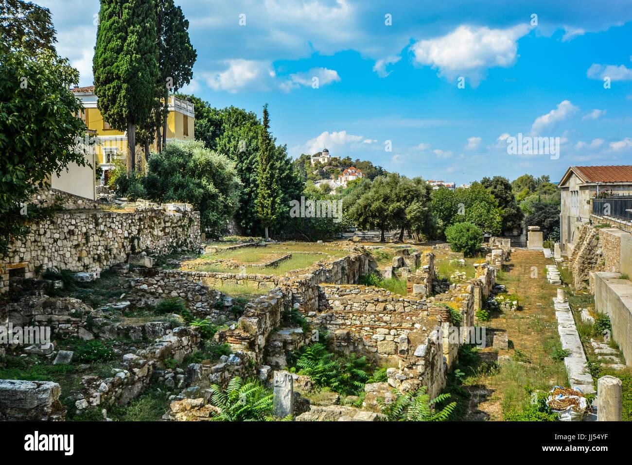 Antike griechische Ruinen in Athen mit einer Kirche und Tempel auf einem Hügel in der Ferne an einem warmen Stockbild
