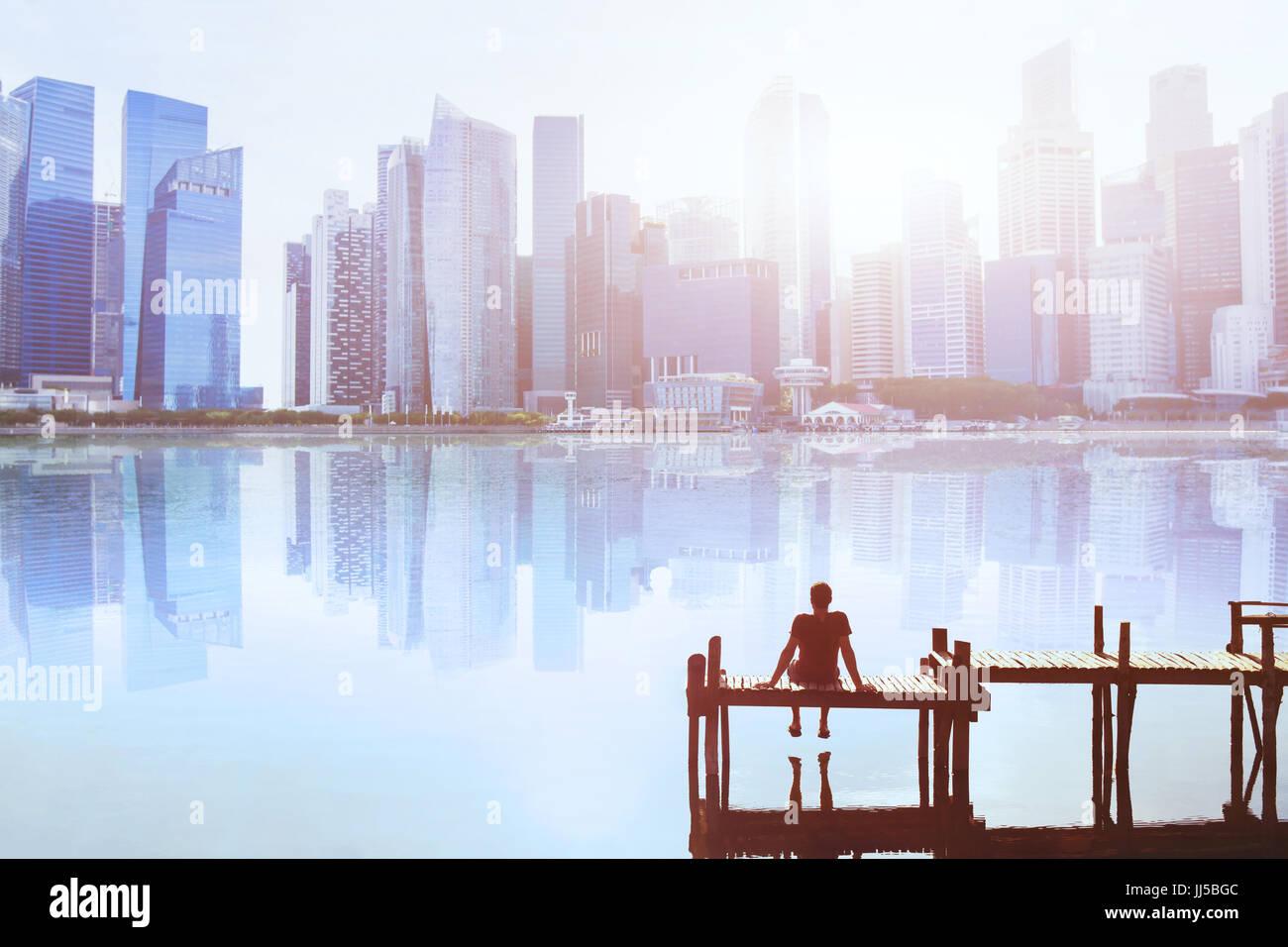 Traum Konzept, Mann auf dem Steg sitzen und genießen Sie modernen Stadtbild Skyline Blick Stockbild