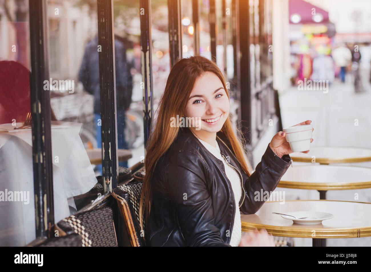Glücklich lächelnde Frau trinkt Kaffee in Straßencafés und auf Kamera, gute Laune Stockbild