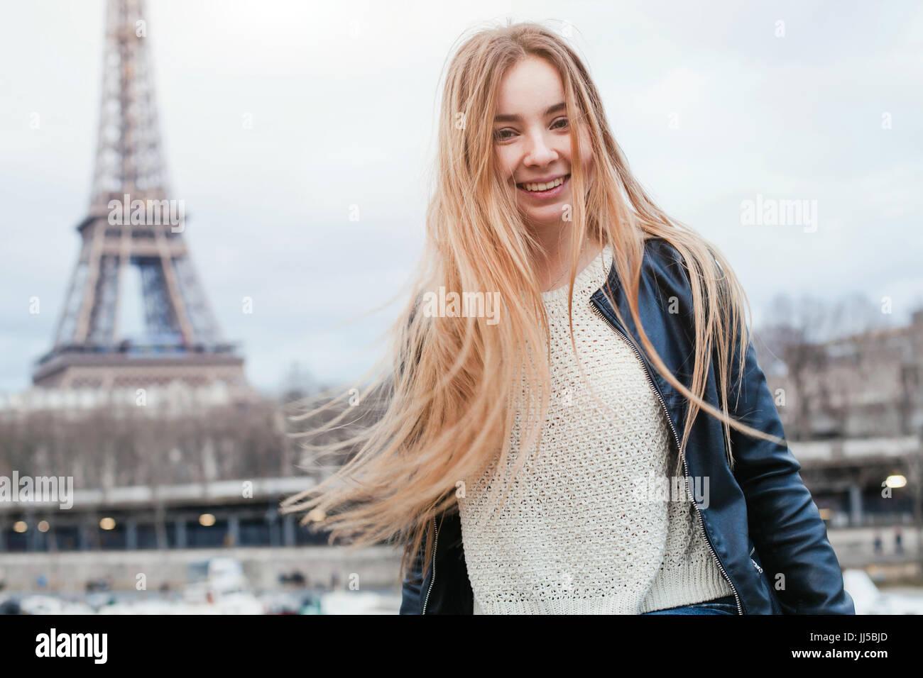 Glückliche junge Frau in Paris in der Nähe von Eiffelturm, lächelnde Mädchen reisen Portrait, Student in Europa Stockfoto