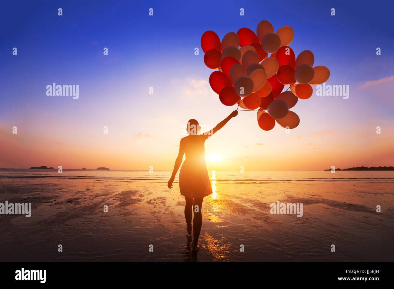 Inspiration, Freude und Glück Konzept, Silhouette der Frau mit vielen fliegenden Ballons am Strand Stockbild