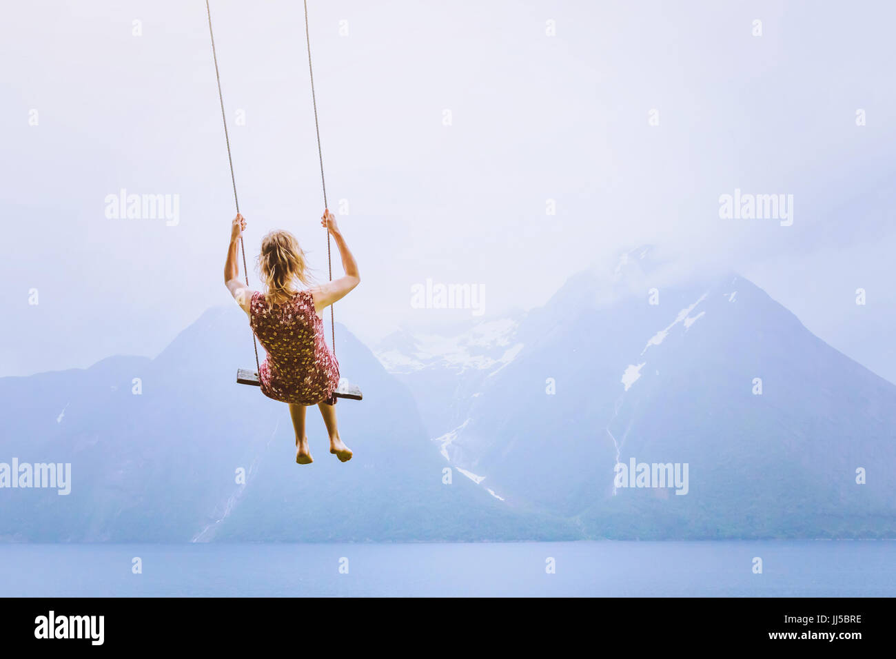 Glück-Konzept, glückliches Mädchen auf der Schaukel auf schöne Landschaft Gebirgshintergrund Stockbild