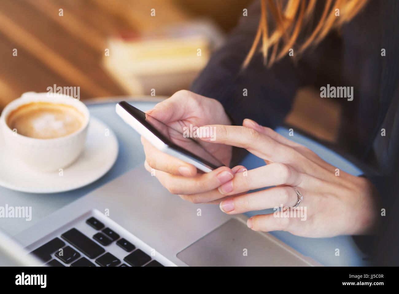 Nahaufnahme von Händen mit mobilen Anwendung auf Smartphone, Frau e-Mails auf ihrem Smartphone im café Stockbild