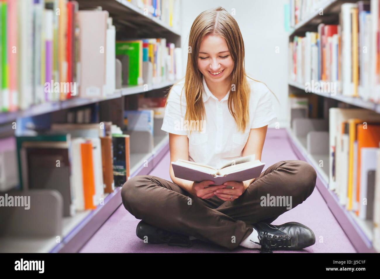 Schüler lesen Buch in der Bibliothek, glücklich lächelnde Frau, Ausbildung Stockbild