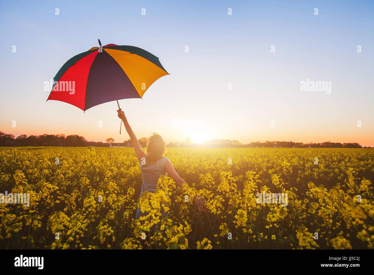 glückliche Frau mit bunten Regenschirm am Sonnenuntergang Blumenfeld, Freude-Konzept Stockbild