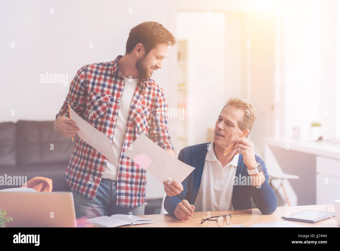 Positive Kollegen helfen einander im Büro Stockbild