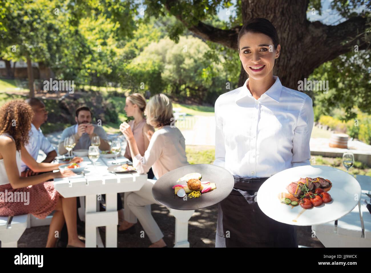 Porträt von lächelnden Kellner Holding Platten von Lebensmitteln im restaurant Stockbild