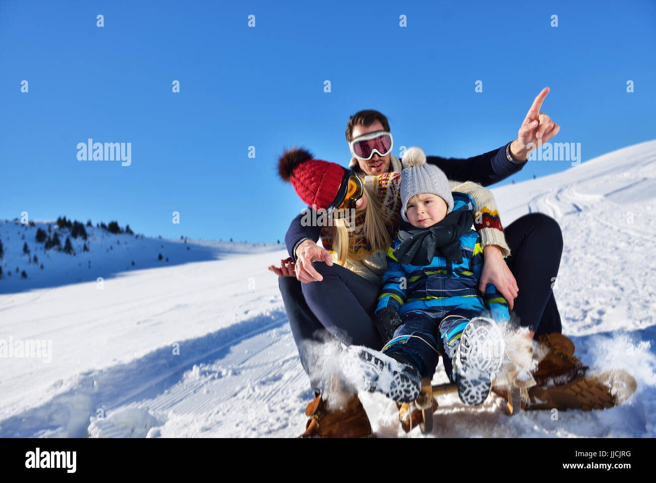 die glückliche Familie fährt den Schlitten im Winter Holz, fröhliche Winter-Unterhaltung Stockbild