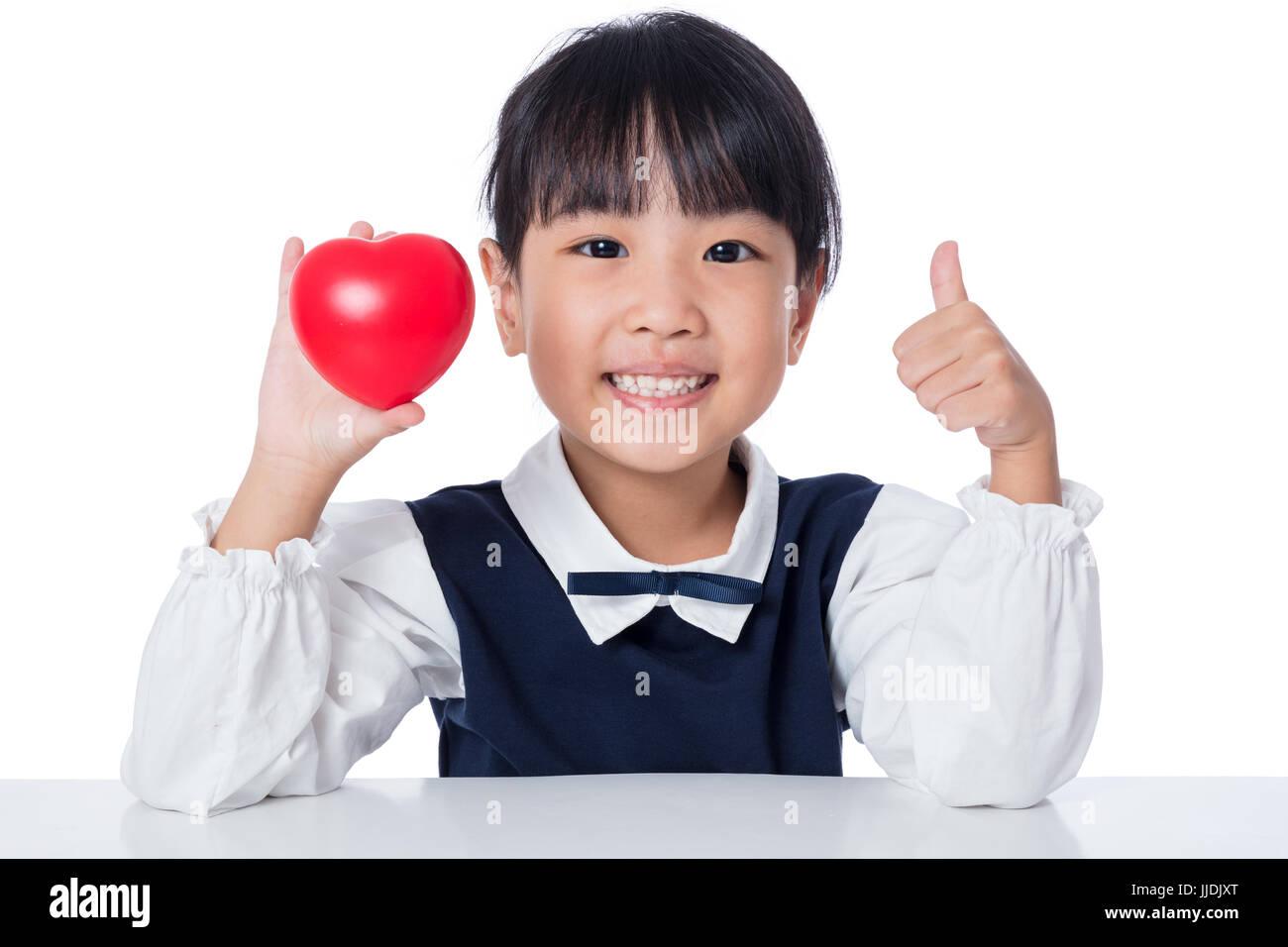 Asiatische chinesische Mädchen halten Rote Herzchen in isolierten weißen Hintergrund Stockfoto