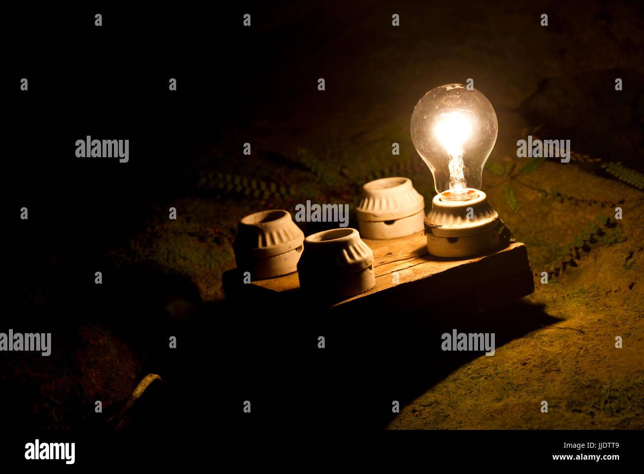 eine Glühbirne von vier anderen. Eine Metapher für die richtige Entscheidung. Stockbild