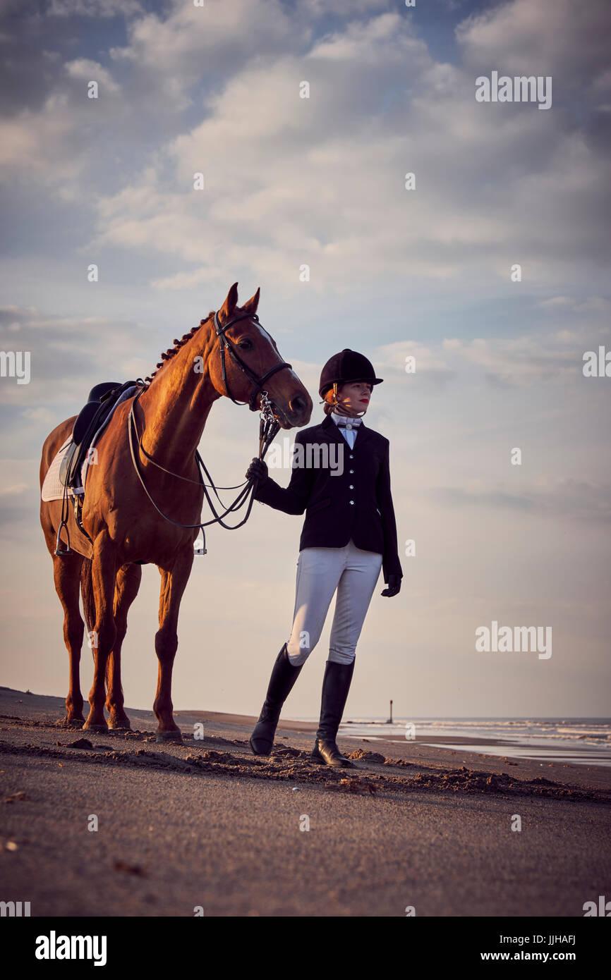 Eine junge Frau mit ihrem Pferd am Strand. Stockbild