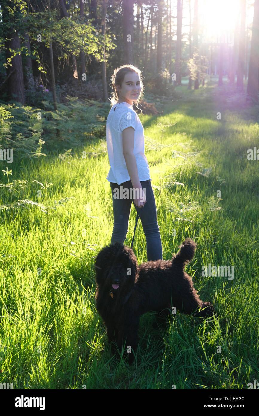 Ein junges Mädchen mit ihrem Hund in einem sonnendurchfluteten Wald stehen. Stockbild