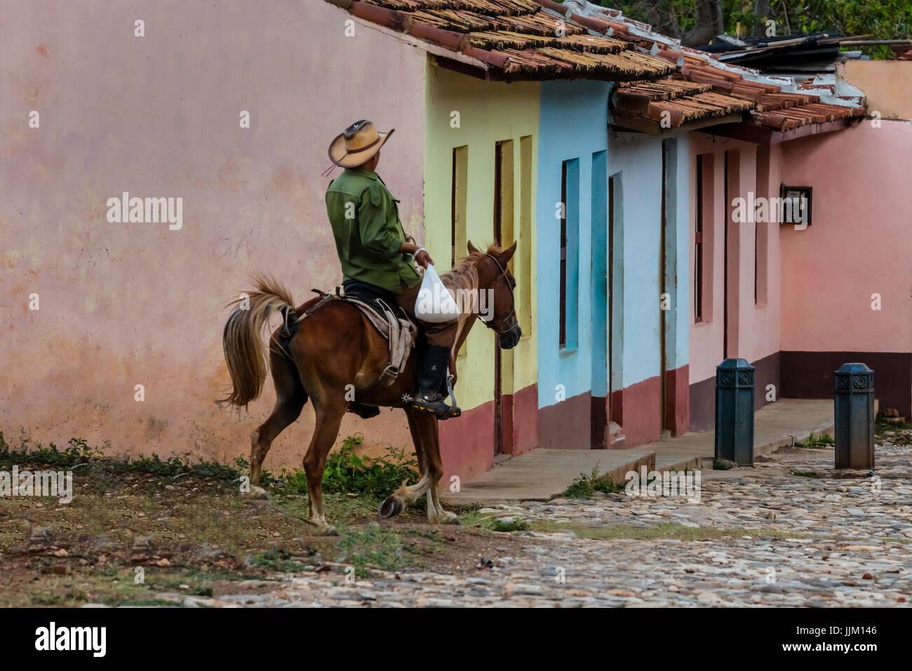 Pferde und Cowboys sind einem gemeinsamen Standort auf die gepflasterten Straßen von TRINIDAD, Kuba Stockbild