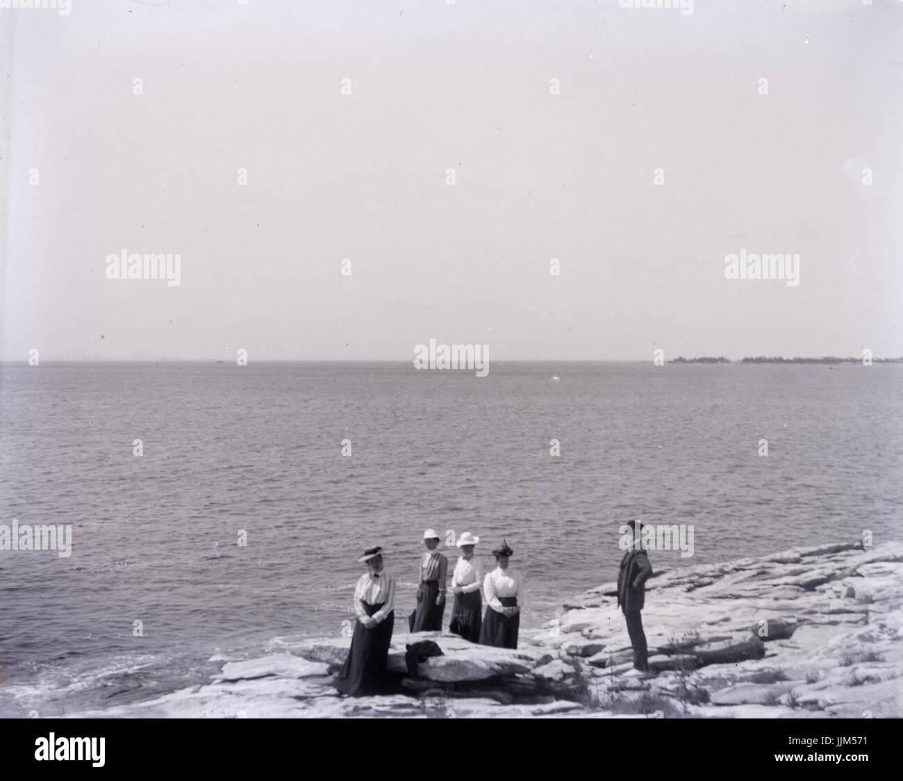 Antike c1910 Foto, fünf Personen an einem küstennahen Standort. Ort unbekannt, möglicherweise Rhode Island, USA. Stockfoto