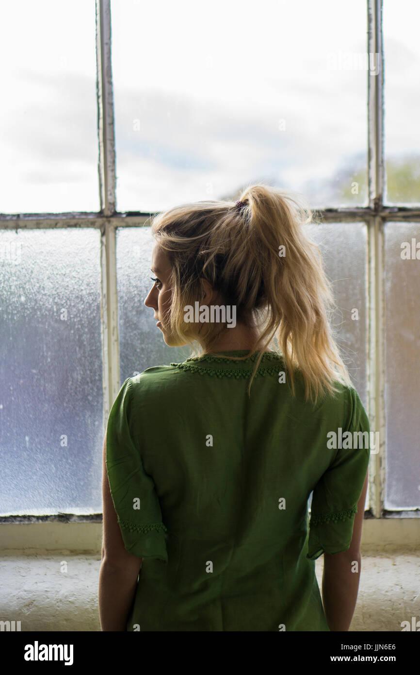 Rückansicht einer jungen blonden Frau am Fenster stehend Stockbild