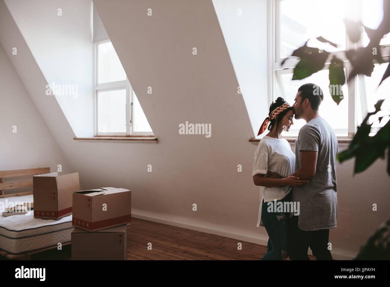 Innenaufnahme des jungen Liebespaar Einzug in ihr neues Zuhause. Mann und Frau in Liebe stehen zusammen mit Kartons Stockbild