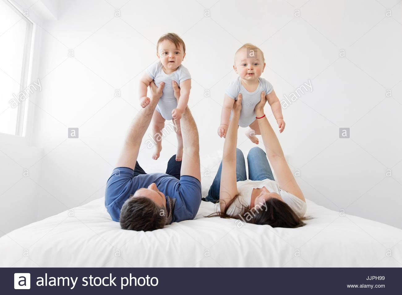 Mann und Frau nebeneinander liegend auf dem Rücken auf einem Bett, jeden Betrieb empor Babyjungen. Stockbild