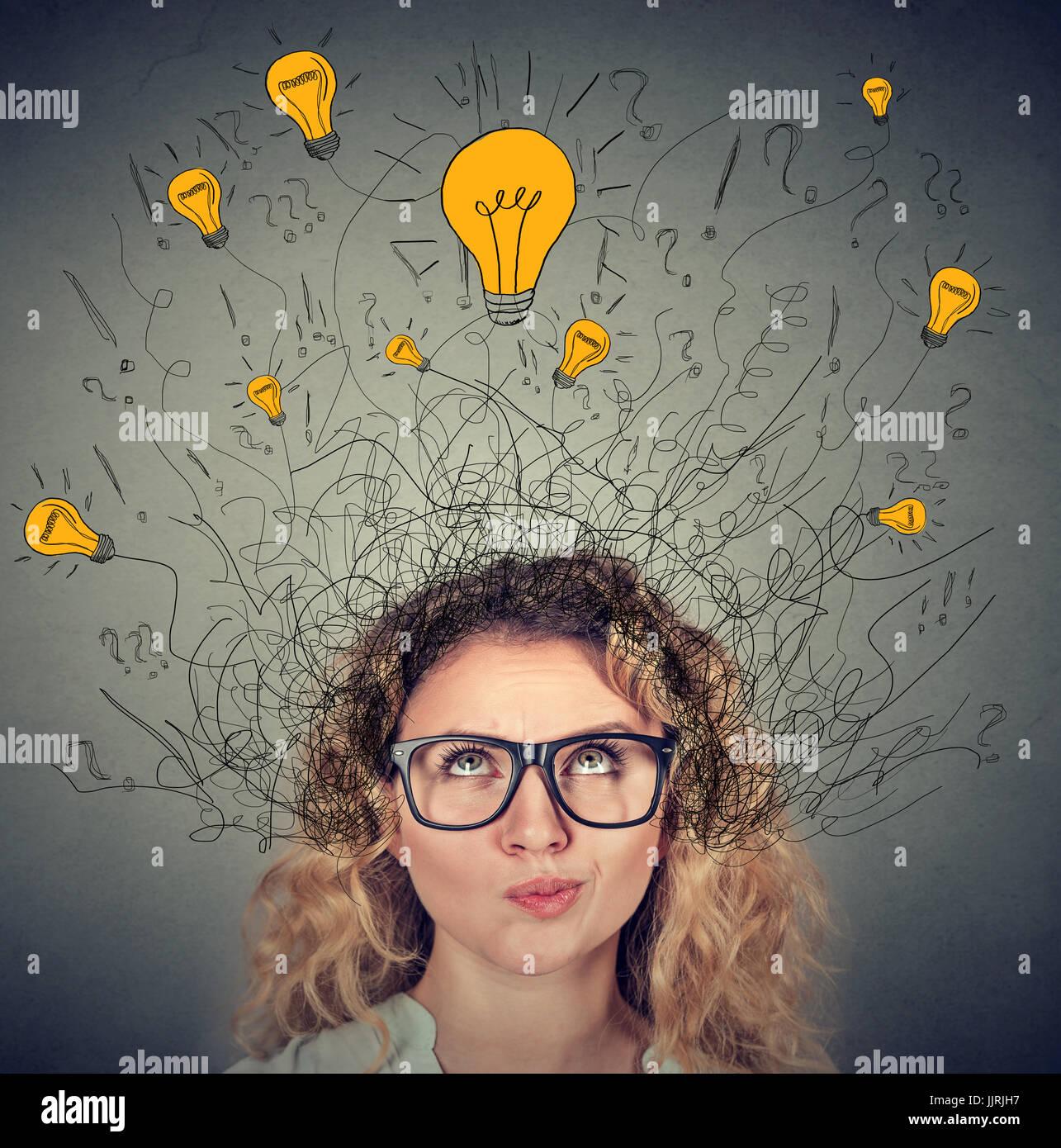 Nachdenkliche Frau in Gläsern mit vielen Ideen, die Glühbirnen über Kopf nach oben isoliert auf graue Stockbild