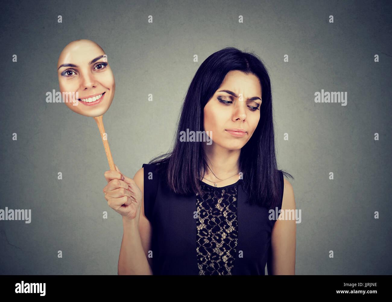 Junge Frau mit traurigen Ausdruck einer Maske mit dem Ausdruck ihrer Fröhlichkeit Stockbild