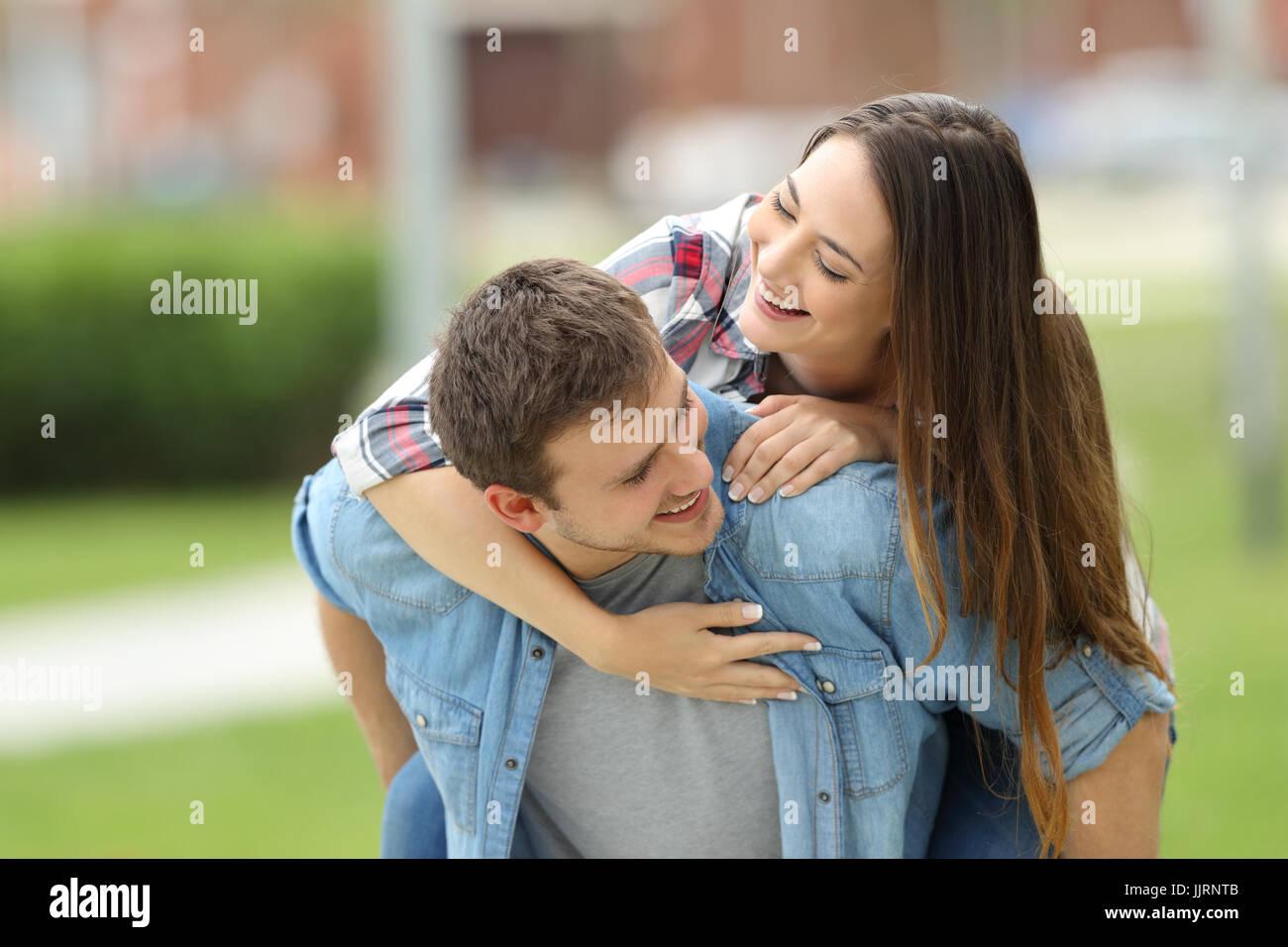Vorderansicht des ein glückliches Paar Teens Spaß zusammen Huckepack im Freien in einem Park mit einem grünen Hintergrund Stockfoto