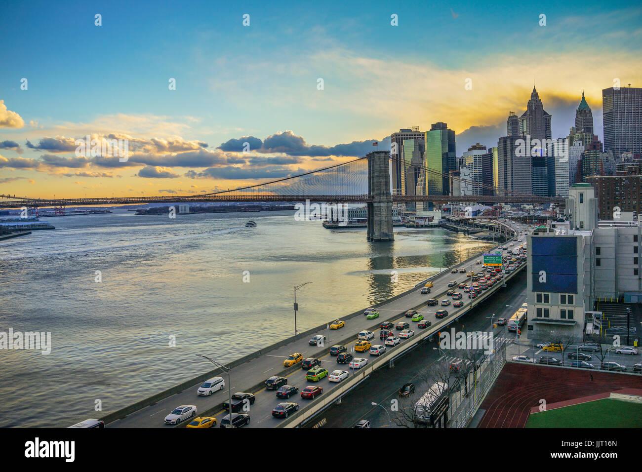 Manhattan Bridge und die Skyline von NYC während des Sonnenuntergangs mit Verkehr Stockbild