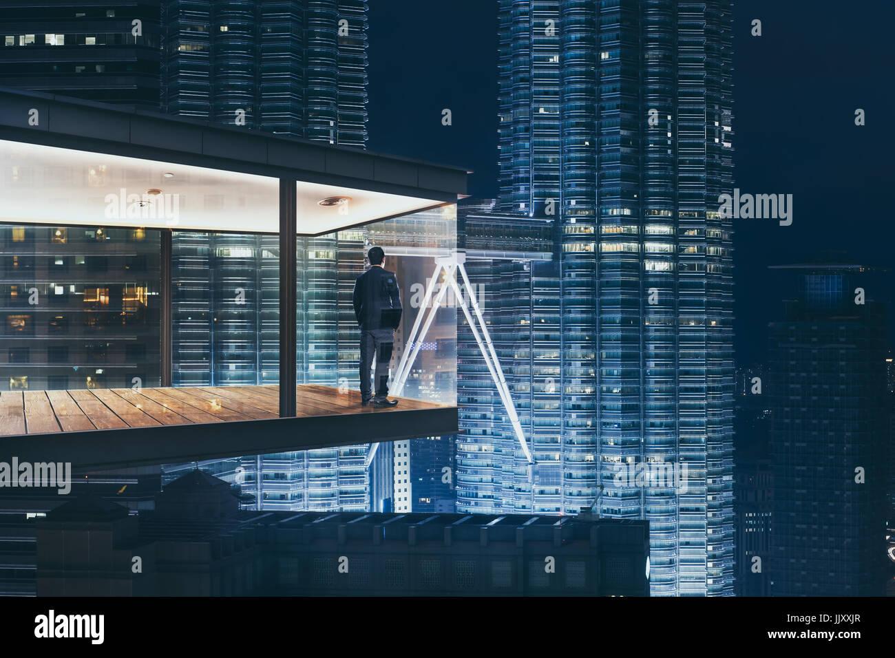 Geschäftsmann in einem modernen Himmel Büro bei Nacht mit Blick auf die schöne Stadt Skyline. Stockbild