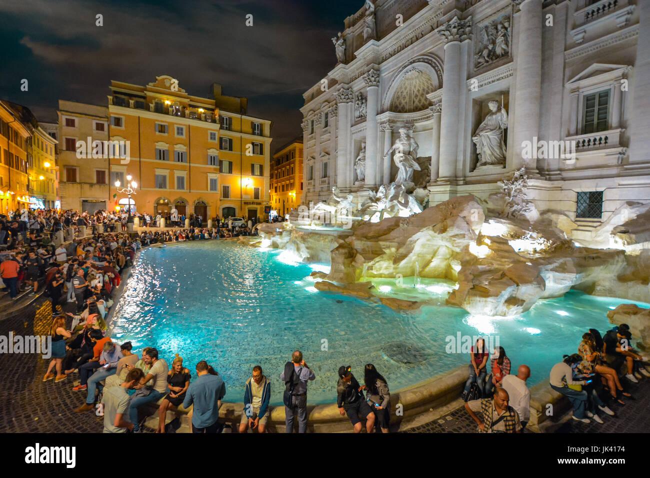 Der Trevi-Brunnen in Rom Italien beleuchtet bunt am Abend mit Touristen rund um es an einem warmen Sommerabend. Stockbild