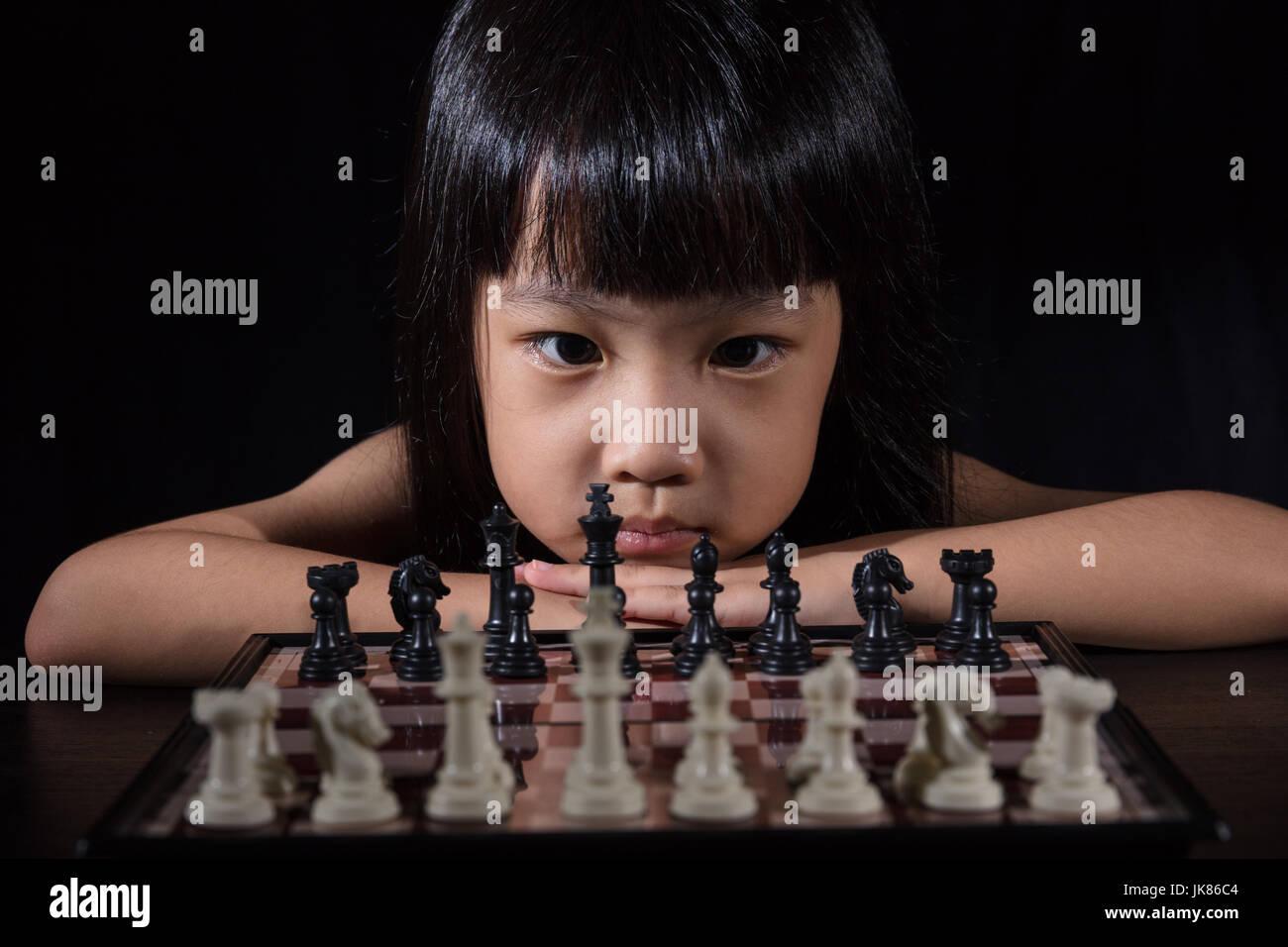 Kleine chinesische Asiatin spielt Schach in isolierten schwarzen Hintergrund Stockbild