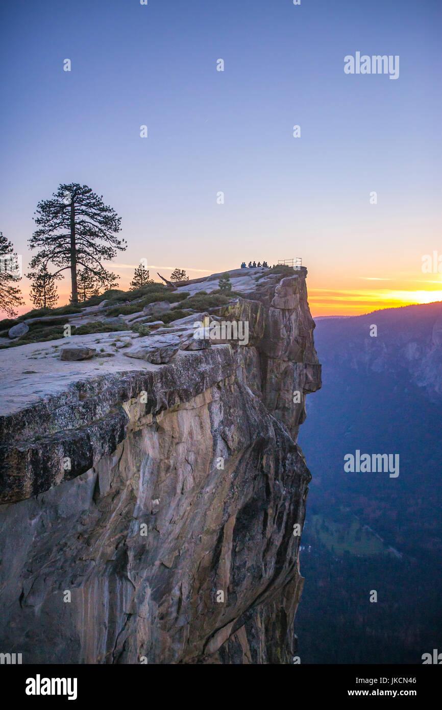 Eine kleine Gruppe von Menschen sitzen an Taft Point in Yosemite bei Sonnenuntergang. Stockbild