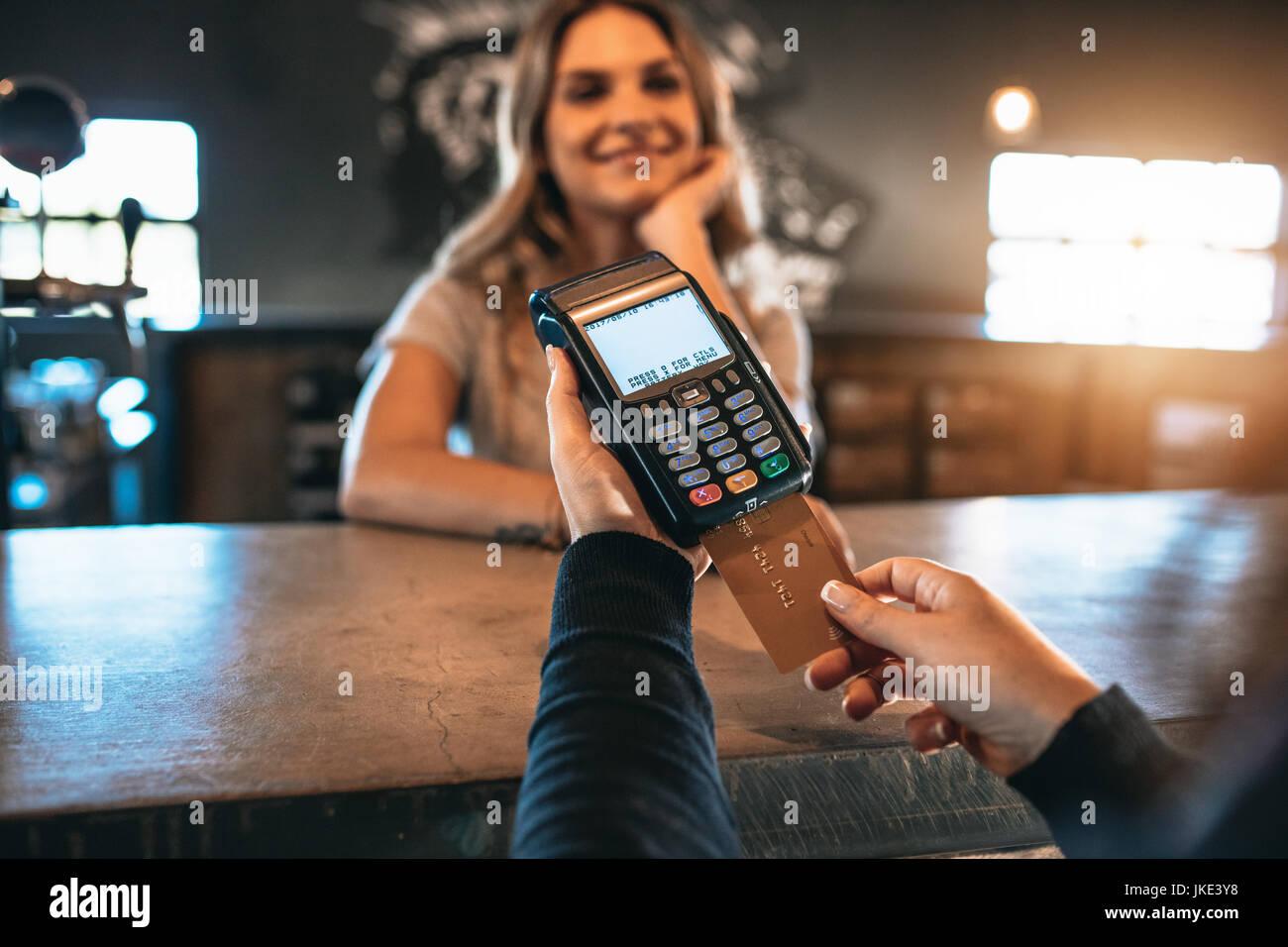 Zugeschnittenes Bild des Mannes, die Zahlung mit einer Kreditkarte Karte in bar mit Frau hinter der Theke. Bargeldloses Stockbild