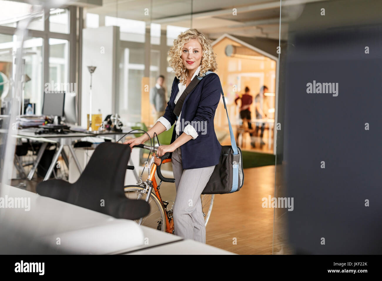 Portrait der Frau mit dem Fahrrad im Büro Stockbild