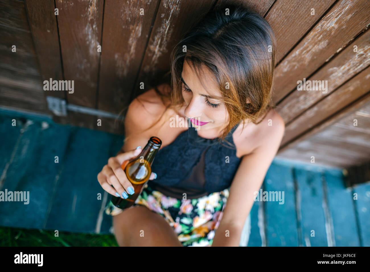 Junge Frau mit Bier an der Holzhütte sitzen Stockbild