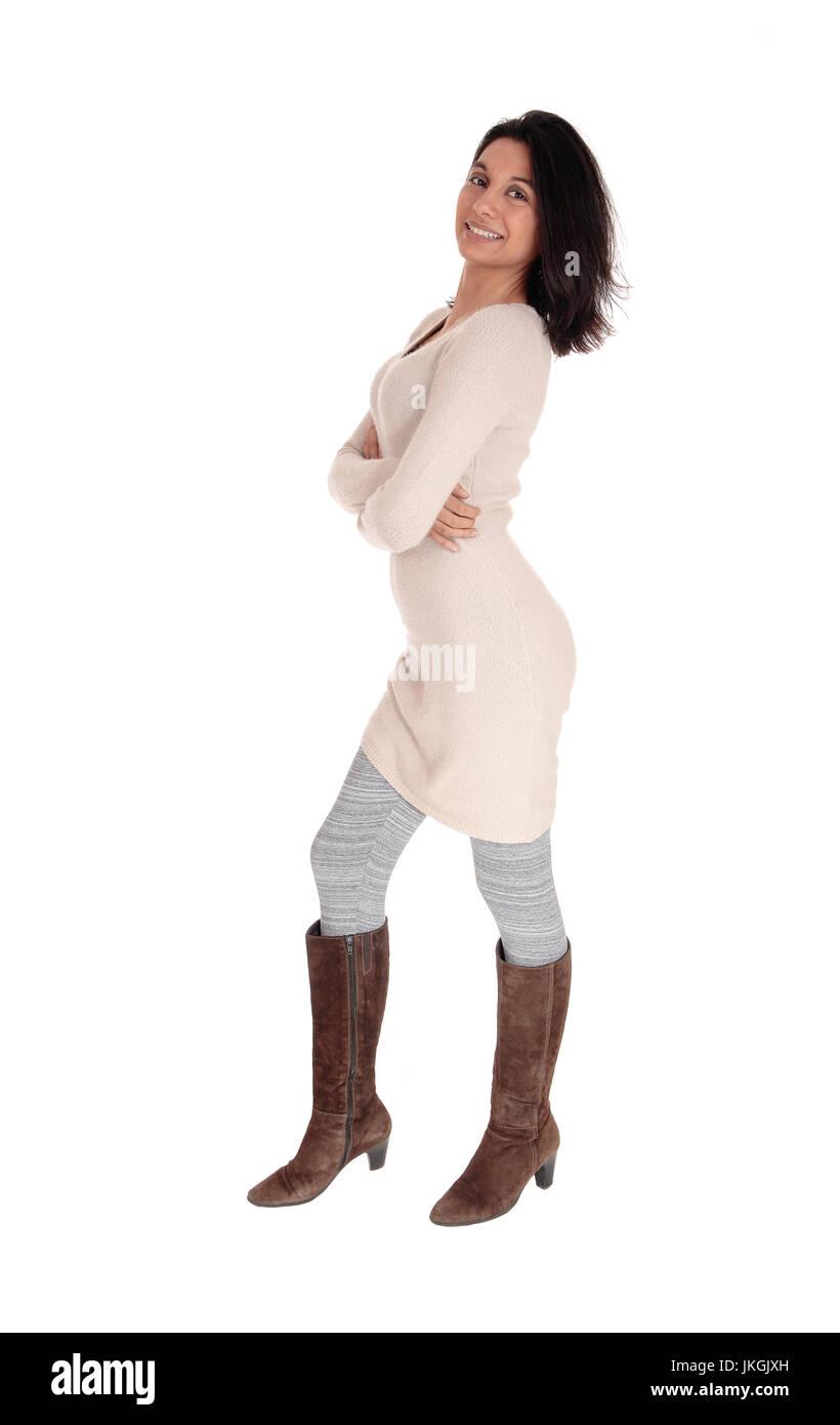 8b3fefc2204 Eine junge Hispanic Frau im Profil in ein Strickkleid Beige und grau  Leggings und braune Stiefel für weißen Hintergrund isoliert.