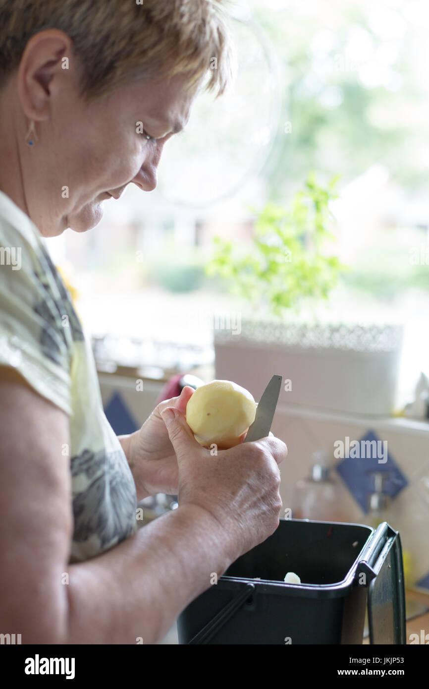 Ältere Frau schneidet geschälte Kartoffel, Zubereitung von Speisen. Vertikale Ausrichtung mit selektiven Fokus auf Stockfoto