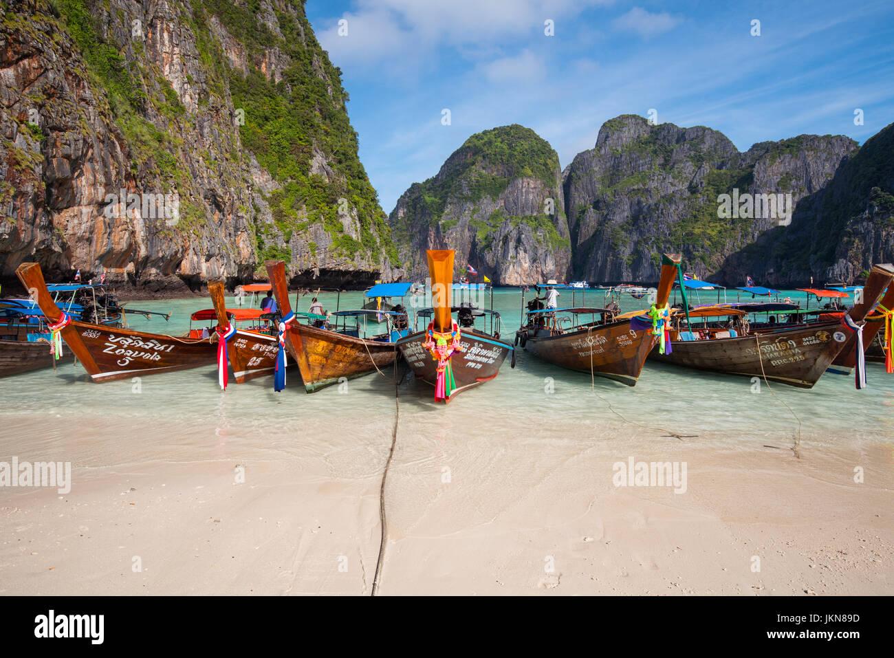 KRABI, THAILAND - 4. Dezember: Bunte Longtailboote am Strand auf einem Hintergrund des blauen Himmels und azurblauen Stockbild