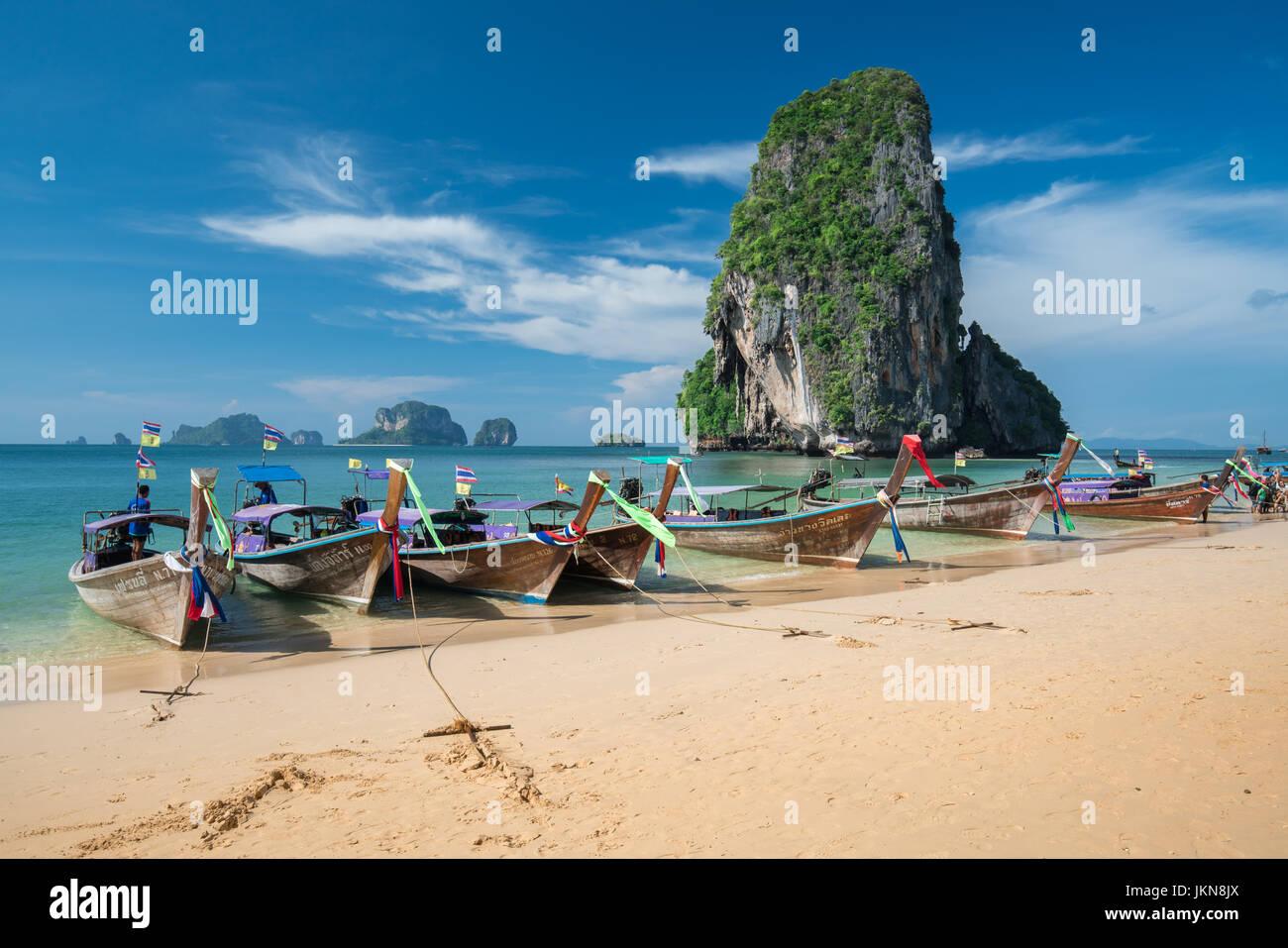 KRABI, THAILAND - 5 Dezember: Bunte Longtailboote an schönen Ao Nang Strand auf einem Hintergrund des blauen Stockbild