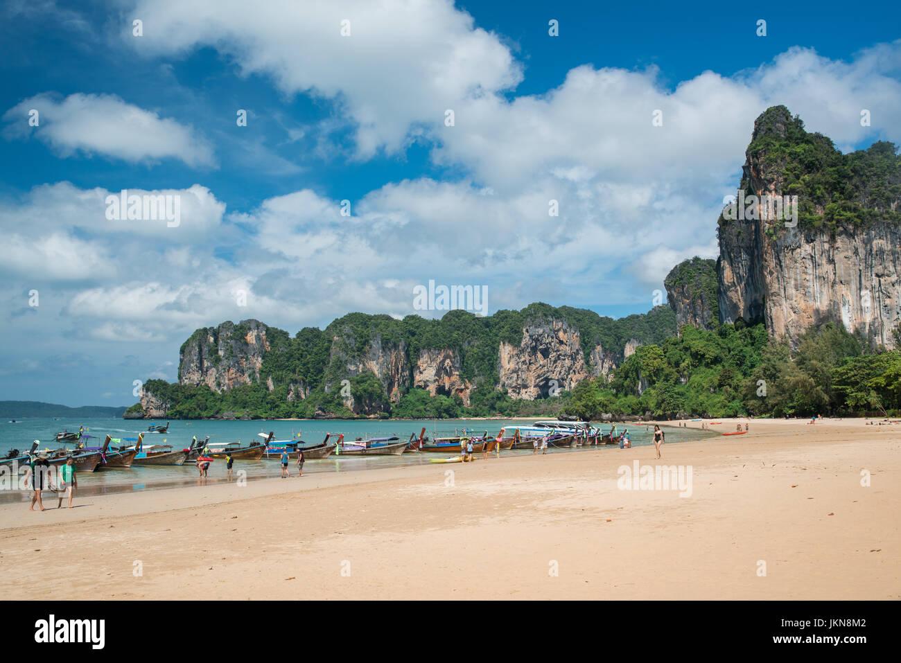 KRABI, THAILAND - 5 Dezember: Bunte Longtailboote am Railay Beach auf einem Hintergrund des blauen Himmels und azurblauen Stockbild